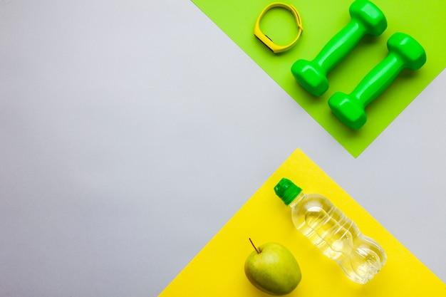 Bovenaanzicht fitnessapparatuur en een fles water Gratis Foto