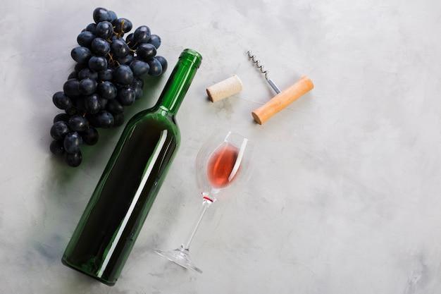 Bovenaanzicht fles rode wijn en druiven Gratis Foto