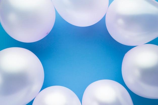 Bovenaanzicht frame met ballonnen en blauwe achtergrond Gratis Foto