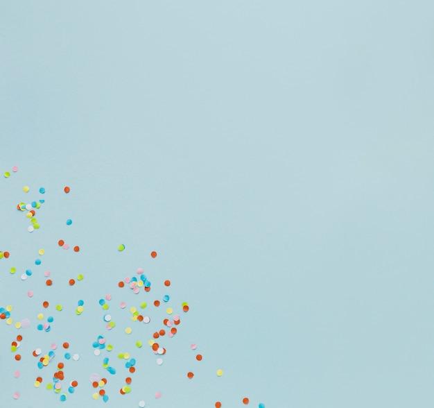 Bovenaanzicht frame met confetti op blauwe achtergrond Gratis Foto