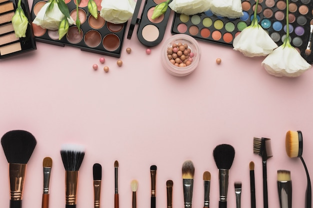 Bovenaanzicht frame met make-up paletten en borstels Gratis Foto