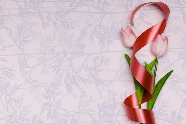 Bovenaanzicht frame met tulpen en rood lint Gratis Foto