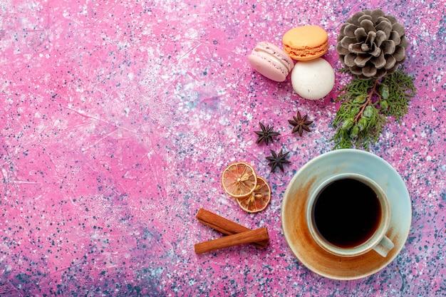 Bovenaanzicht franse macarons heerlijke kleine cakes met thee op roze oppervlak Gratis Foto