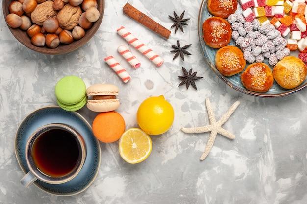 Bovenaanzicht franse macarons met kopje thee op lichte witte ondergrond Gratis Foto