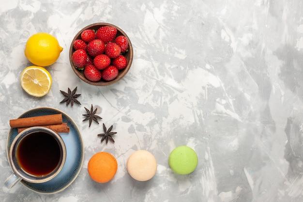 Bovenaanzicht franse macarons met thee en verse aardbeien op witte ondergrond Gratis Foto