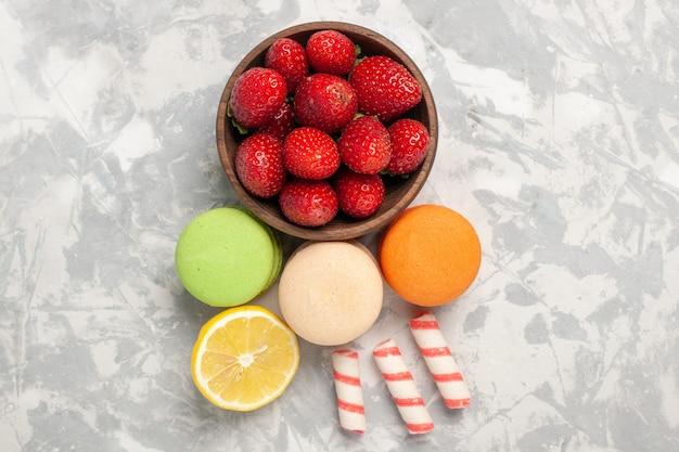 Bovenaanzicht franse macarons met verse rode aardbeien op witte ondergrond Gratis Foto