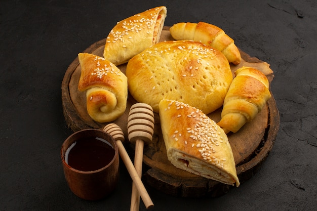 Bovenaanzicht gebak en croissants op het bruine bureau en de donkere achtergrond Gratis Foto
