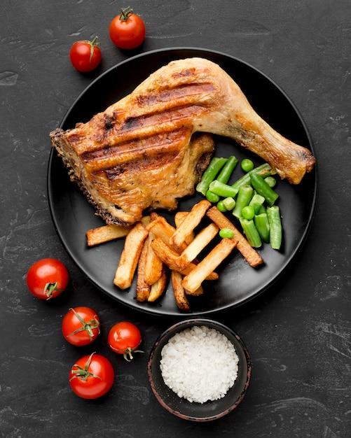 Bovenaanzicht gebakken kip en aardappelen op plaat met tomaten Gratis Foto