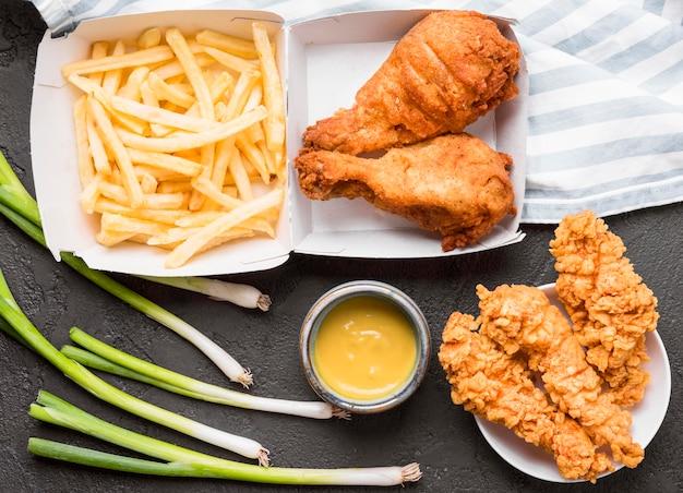 Bovenaanzicht gebakken kip en frietjes met saus Gratis Foto
