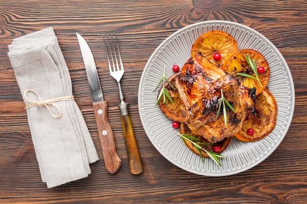 Bovenaanzicht gebakken kip en stukjes sinaasappel op plaat met bestek en servet Gratis Foto