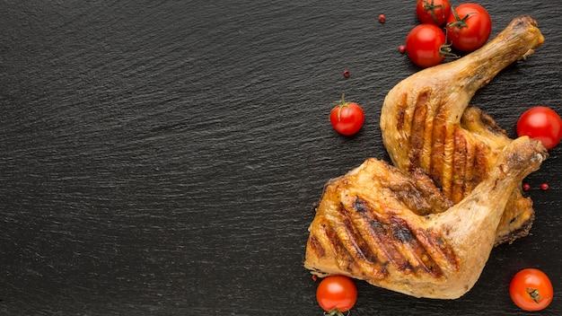 Bovenaanzicht gebakken kip en tomaten met kopie-ruimte Premium Foto