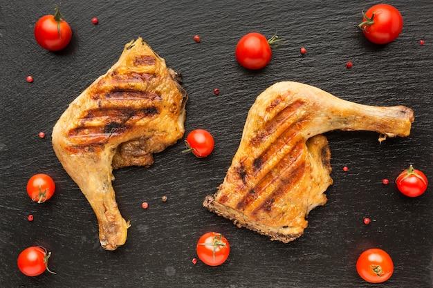 Bovenaanzicht gebakken kip en tomaten Gratis Foto