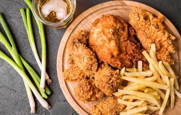 Bovenaanzicht gebakken kip met frietjes op snijplank en groene uien Gratis Foto