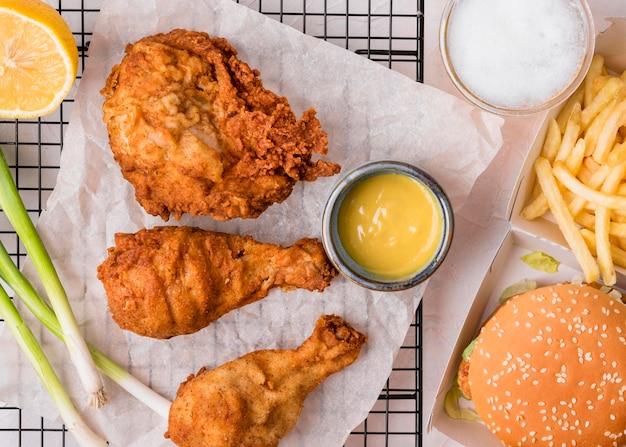 Bovenaanzicht gebakken kip met hamburger en frietjes Gratis Foto