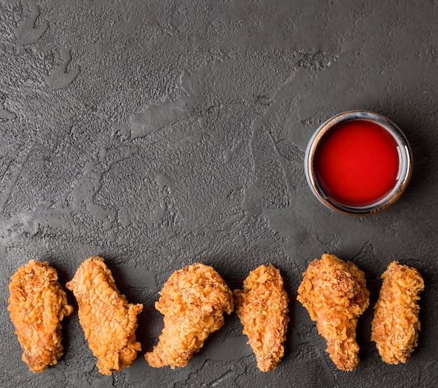 Bovenaanzicht gebakken kippenvleugels met saus en kopie-ruimte Gratis Foto