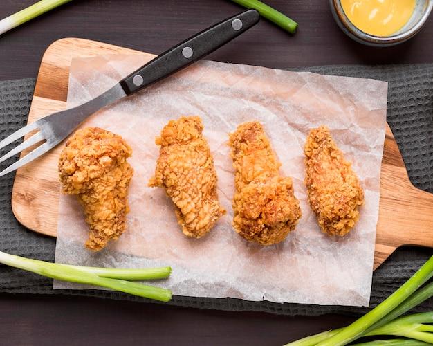 Bovenaanzicht gebakken kippenvleugels op snijplank met groene uien en vork Gratis Foto