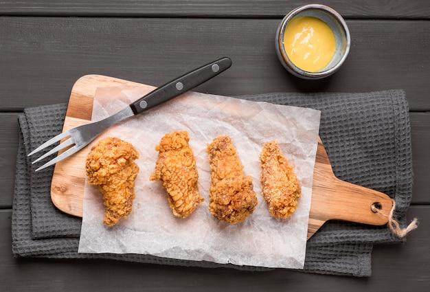Bovenaanzicht gebakken kippenvleugels op snijplank met saus Gratis Foto