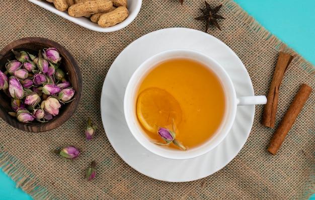 Bovenaanzicht gedroogde toppen met een kopje thee en kaneel op een beige servet Gratis Foto
