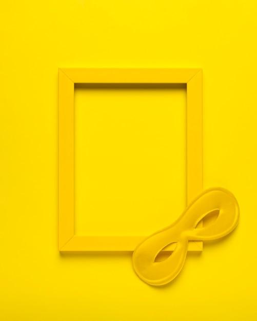 Bovenaanzicht geel carnaval masker met geel frame Gratis Foto