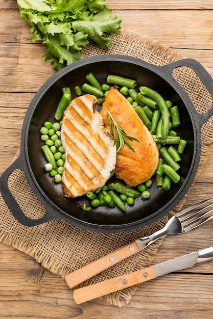 Bovenaanzicht gegrilde kip en erwten in pan met bestek Gratis Foto