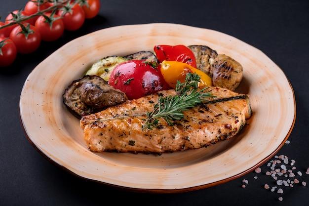 Bovenaanzicht gegrilde steak zalmfilet met groente salade, peper, kruiden op plaat Premium Foto
