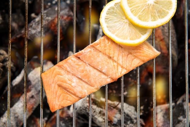 Bovenaanzicht gegrilde zalm met citroen op de vlammende grill. Premium Foto
