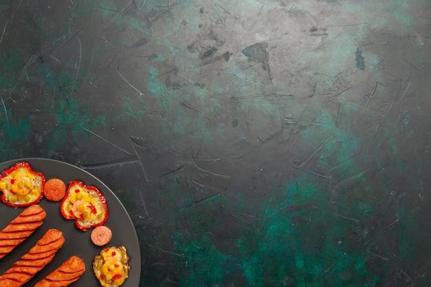Bovenaanzicht gekookte paprika met gebakken worstjes in plaat op donkergroen oppervlak Gratis Foto