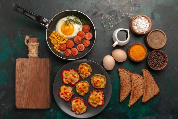 Bovenaanzicht gekookte paprika met roerei, brood, brood en worst op donkergroen oppervlak Gratis Foto