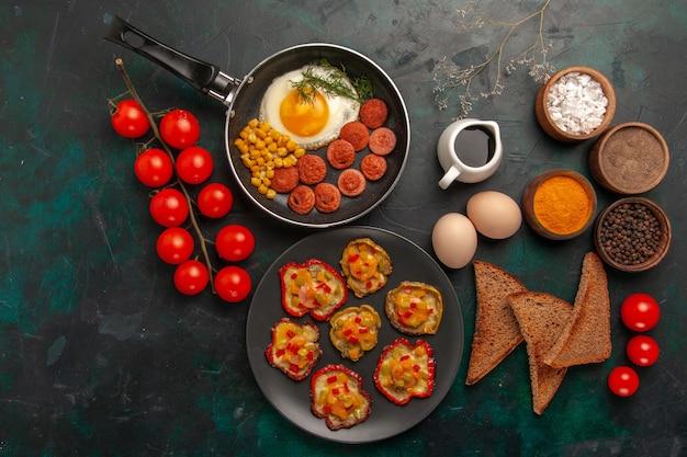 Bovenaanzicht gekookte paprika met roerei brood en worst op het donkergroene oppervlak Gratis Foto