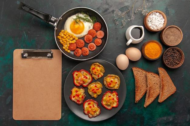 Bovenaanzicht gekookte paprika met roerei en worst op donkergroen oppervlak Gratis Foto