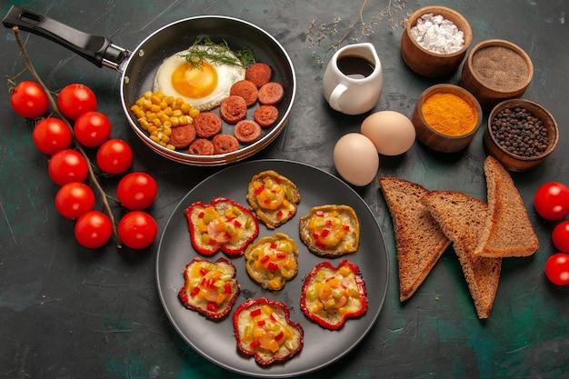 Bovenaanzicht gekookte paprika met roerei, kruiden en worstjes op het donkergroene oppervlak Gratis Foto