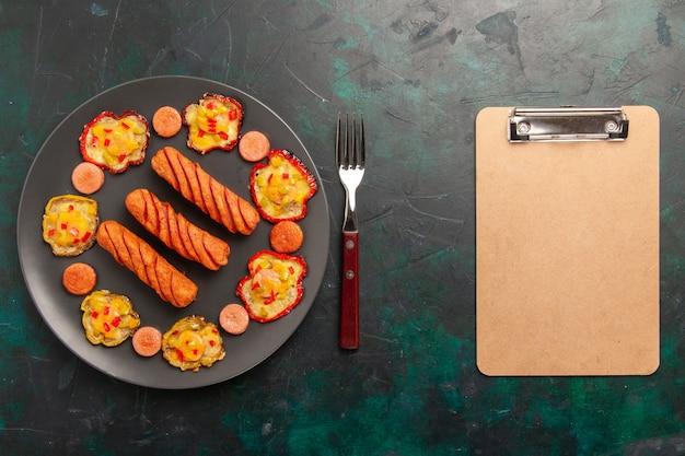 Bovenaanzicht gekookte paprika met worst en blocnote op donkergroen oppervlak Gratis Foto