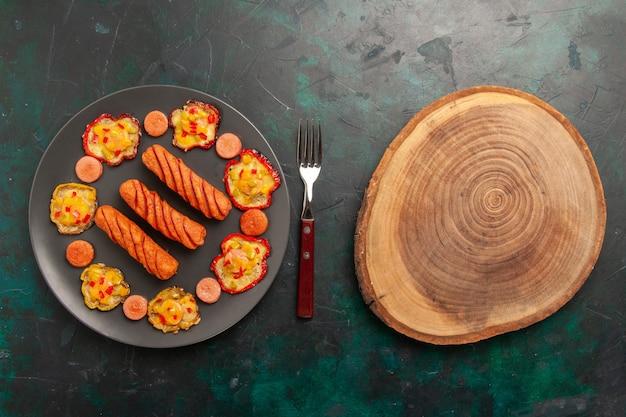 Bovenaanzicht gekookte paprika met worst en houten bureau Gratis Foto