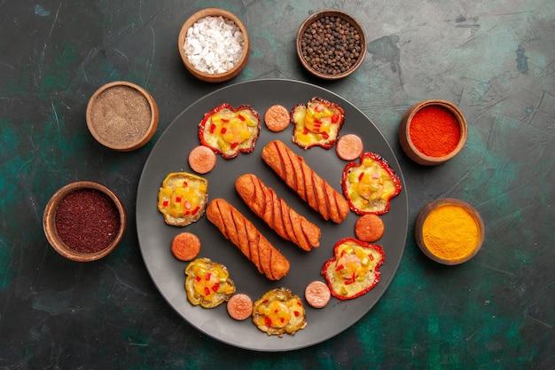Bovenaanzicht gekookte paprika met worst en kruiden op het donkergroene oppervlak Gratis Foto