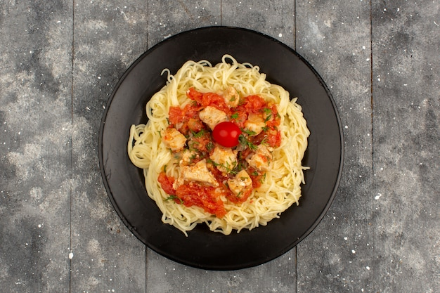 Bovenaanzicht gekookte pasta met tomatensausen en gesneden kippenvleugels in zwarte plaat op de grijze rustieke houten vloer Gratis Foto
