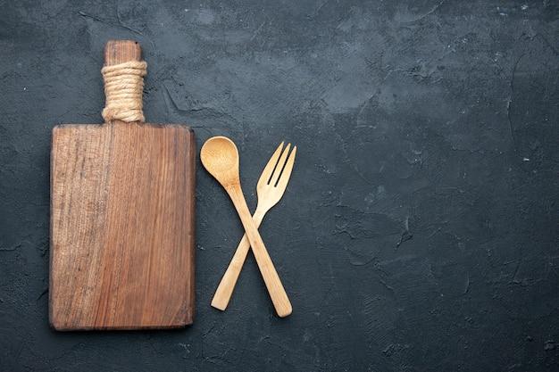 Bovenaanzicht gekruiste houten lepel en vork bord op donkere tafel met kopie plaats Gratis Foto