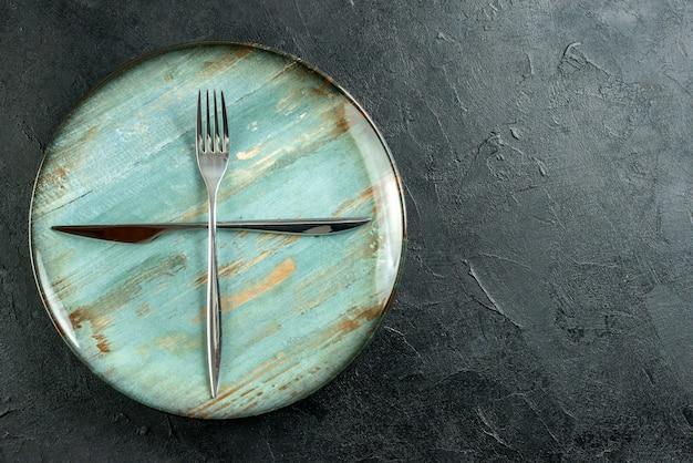 Bovenaanzicht gekruiste vork en mes op cyaan ronde plaat op donkere tafel kopie plaats Gratis Foto