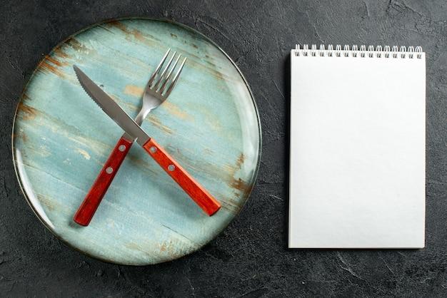 Bovenaanzicht gekruiste vork en mes op notebook met ronde plaat Gratis Foto