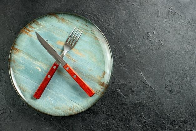 Bovenaanzicht gekruiste vork en mes op ronde plaat notebook op donkere grond met kopie plaats Gratis Foto