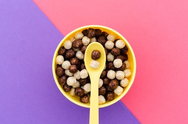Bovenaanzicht gele lepel met kom chocoladegranen Gratis Foto