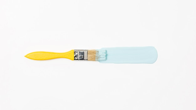 Bovenaanzicht gele penseel met blauwe verf Premium Foto