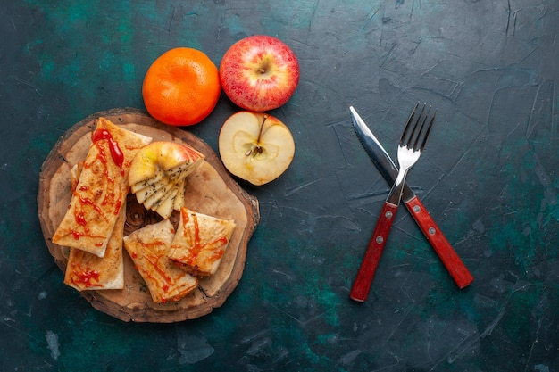 Bovenaanzicht gerolde pita deeg gesneden met saus en fruit op het donkerblauwe bureau Gratis Foto