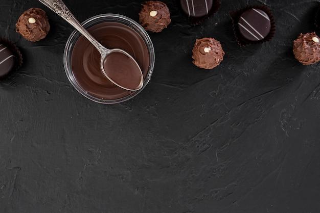 Bovenaanzicht gesmolten chocolade en snoepjes met kopie ruimte Gratis Foto