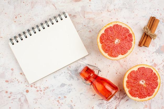 Bovenaanzicht gesneden grapefruits kaneelstokjes fles kladblok op naakt oppervlak Gratis Foto