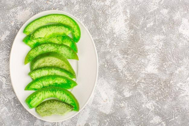 Bovenaanzicht gesneden groene komkommers binnen plaat op wit oppervlak Gratis Foto