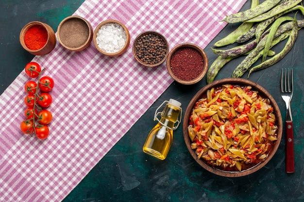 Bovenaanzicht gesneden groente maaltijd heerlijke bonen maaltijd met verschillende kruiden op de blauwe achtergrond Gratis Foto