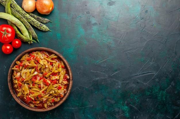 Bovenaanzicht gesneden groentemaal met verschillende ingrediënten binnen plaat op donkerblauwe achtergrond Gratis Foto
