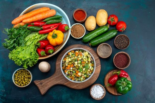 Bovenaanzicht gesneden groentesalade gepeperd met kip plakjes binnen plaat met verse groenten op blauw bureau snack lunch salade plantaardig voedsel Gratis Foto