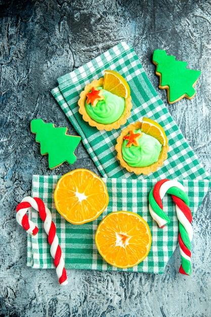 Bovenaanzicht gesneden sinaasappelen kerstboom snoepjes kleine taartjes op groen wit geruite keukenhanddoek op grijze tafel Gratis Foto