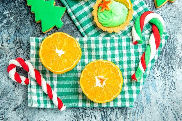 Bovenaanzicht gesneden sinaasappelen kerstboom snoepjes op groen wit geruite keukenhanddoek op grijze tafel Gratis Foto